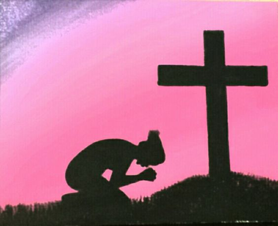 woman kneeling at cross